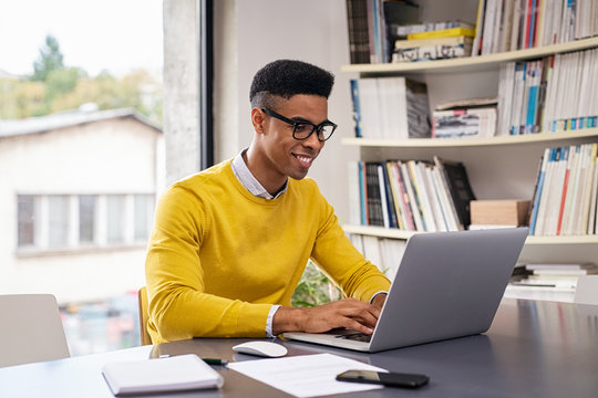 Happy young businessman working on laptop