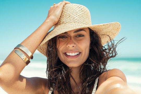 Happy woman wearing straw hat at summer beach