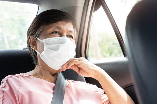 Asian Elderly woman Passenger wear protective or surgical mask for prevent coronavirus or Covid-19 while sitting in car.
