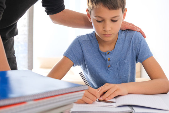 Kid sitting at the table with many books notebooks and doing homework. Mother helping him. Learning difficulties, learning at home, education, motivation concept