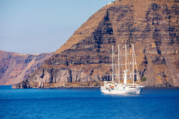 Sailboat in the sea over beautiful big mountains background, luxury summer adventure, active vacation in Santorini, Greece