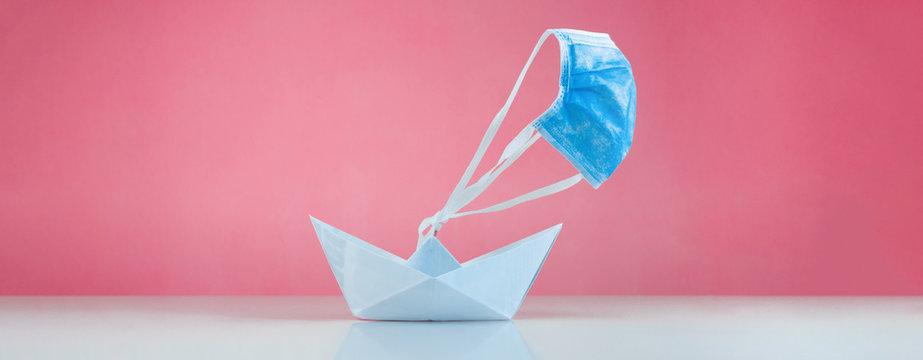 Barca di carta con mascherina chirurgica per vela. Concetto di Estate con Coronavirus.