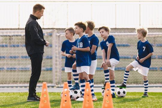Young coach explaining training rules to children school soccer team. Kids in football team listening to coach. Boys on soccer practice. Physical education outdoor class
