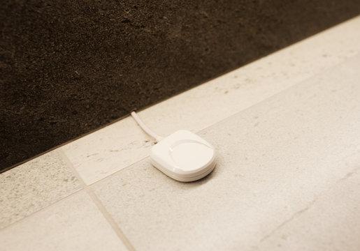 anti-flooding sensor on white floor in the bathroom