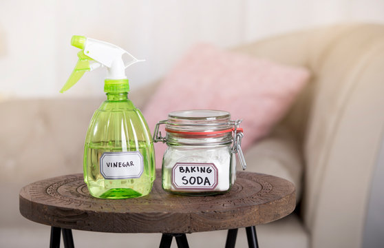 Using baking soda Sodium bicarbonate and white vinegar for home cleaning. White vinegar in spray bottle and baking soda in glass jar.