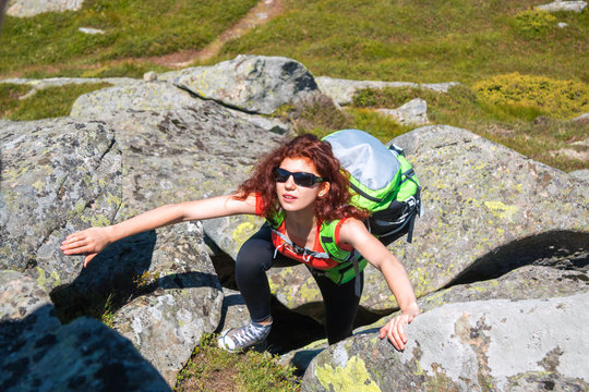 Caucasian girl in sunglass with red hair climbing on the stones in mountain