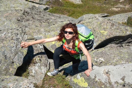 Caucasian girl in sunglass with red hair climbing at stones in mountain