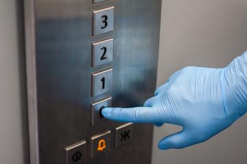 Obraz Przyciskanie przycisku w windzie ręka w rękawiczce - fototapety do salonu