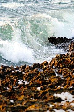 High Angle View Of Waves Rushing Towards Rocks