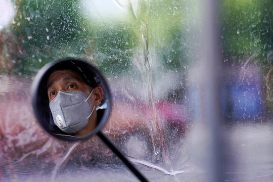 A man wearing a face mask is seen reflected on her electric bike's rearview mirror on a street after the lockdown was lifted in Wuhan