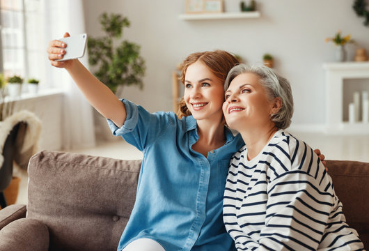 Happy mother and daughter taking selfie on couch.