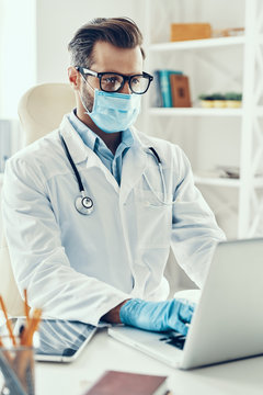 Concentrated young man in white lab coat and protective mask wor