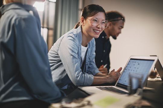 Smiling Asian businesswoman meeting with coworkers in an office