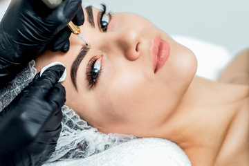 Professional cosmetologist hands are doing permanent makeup on eyebrows of young woman, close up.