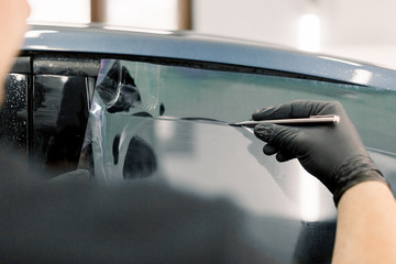 Cropped image of hands of worker in garage tinting a car window with tinted foil or film, holding special blade or knife to cut the film. Car detailing workshop, tinting windows