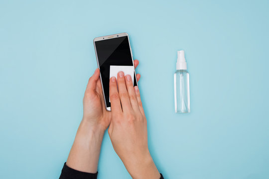 Woman cleaning and disinfecting mobile phone for Covid-19 coronavirus disease prevention.