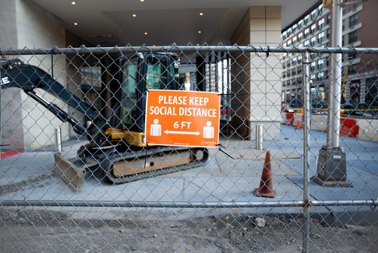 Jersey City, NJ - April 12 2020: A social distancing sign due to COVID-19 Outbreak in a construction area. The Coronavirus pandemic has caused CDC Guidelines to state a 6 Feet space between people