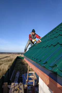 A rooftop worker attaches a metal tile to the roof base.