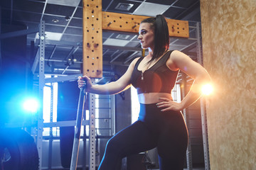 Candid strong young woman is posing with a hammer in the gym, strength training. Real wokout