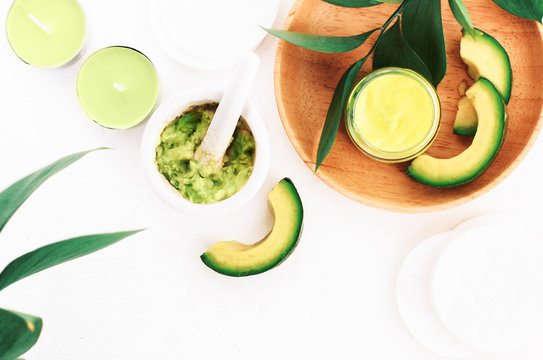 Homemade avocado mask hand made from fresh raw mashed green fruit, face and skin care diy recipe.  Nourishing organic cosmetic ingredients top view white table, preparation for beauty spa.