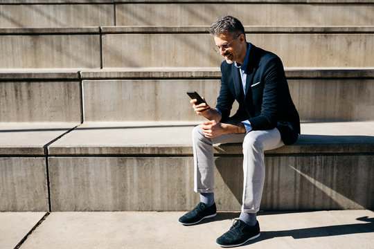 Gray-haired businessman sitting on stairs using cell phone