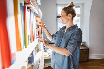 Pregnant woman standing at bookshelf at home
