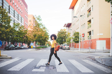 Young woman with afro hairdo walking in the city Fotobehang