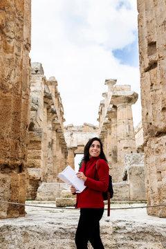 Female tourist walking through the ruins of Paestum, Italy