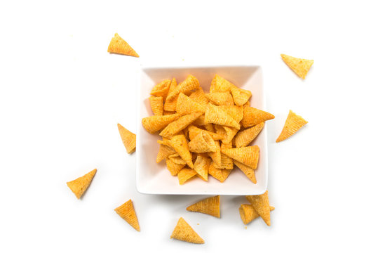 Closeup of bugles salted appetizers in a white bowl on top view on white background