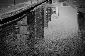 Fotomurales - Reflection Of Buildings In Puddle On Road