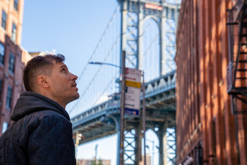 Wall Mural - Young man walking down the Washington street, in Brooklyn with a Manhattan bridge in the background.