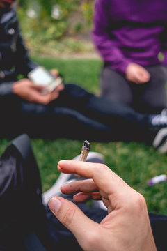 Hand with Marijuana joint (cannabis cigarette) at park in a sunny day, with teen silhouettes over grass at background