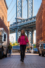 Wall Mural - Young beautiful lady walking down the Washington street, in Brooklyn with a Manhattan bridge in the background.