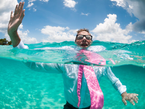 Over-under view of businessman holding his hand up to call for help trying to keep afloat in clear turquoise waters