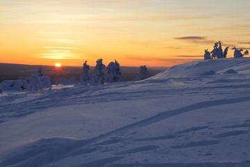 Wintry countryside with sun on horizon in Ylläs in Finnish Lapland