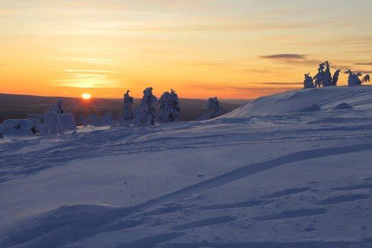 Wintry countryside with sun on horizon in Ylläs in Finnish Lapland