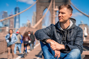 Fototapete - Young man sitting on a  Brooklyn Bridge with a magical Manhattan island view.
