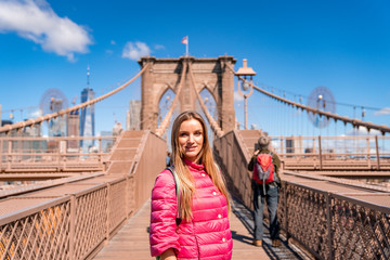 Wall Mural - Young beautiful girl walking down the  Brooklyn Bridge with a magical Manhattan island view.