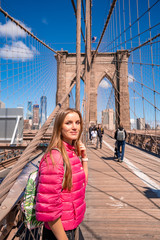 Wall Mural - Young beautiful woman walking down the  Brooklyn Bridge with a magical Manhattan island view.