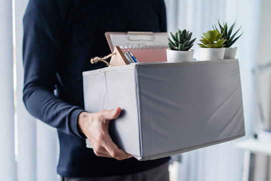 Midsection close up of unknown caucasian man holding a box with personal items stuff leaving the office after being fired from work due recession economic crisis downturn losing job company shutdown