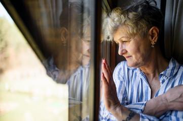 Obraz Sad senior woman standing indoors at home, corona virus and quarantine concept. - fototapety do salonu