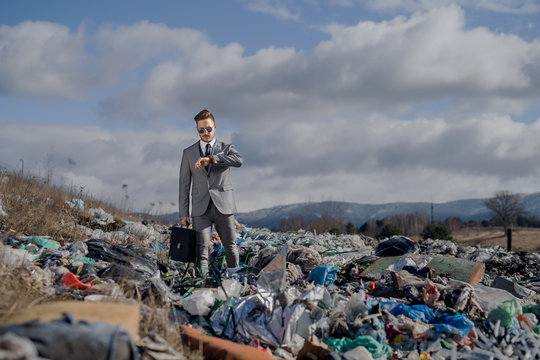 Modern businessman on landfill, consumerism versus pollution concept.