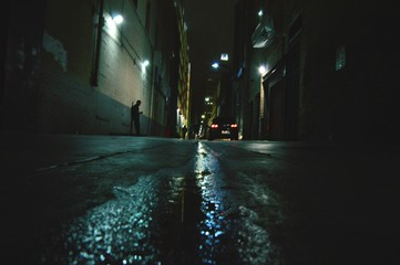 Fototapeta Surface Level Of Alley Amidst Buildings At Night