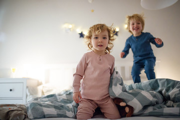 Wall Mural - Two small children jumping on bed indoors at home, having fun.