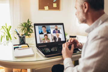 Man working from home having online group videoconference on laptop Wall mural