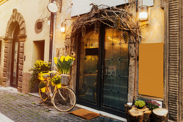 Foto op Aluminium Fiets Beautiful yellow tulips in basket of bicycle on street near cafe. Yellow bicycle. Creative solution, decoration cafe. Traditional italian cafe. Copy space.