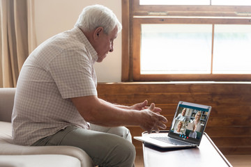 80s elderly man sit on couch talk with friends using pc internet connection and videoconference app. Diverse mature relatives enjoy virtual meeting. Modern technologies videocall communication concept Fotobehang