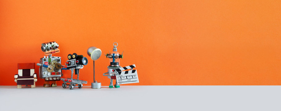 Robotic filmmaking backstage. Two robots shoots motion picture television episode or movie. Funny filmmakers director cameraman, cyborg assistant with clapperboard. Orange gray background, copy space