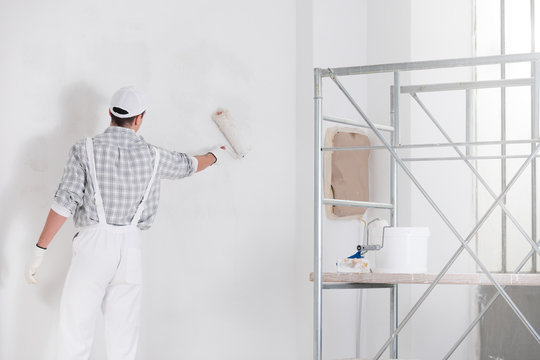 Painter or builder painting a wall white