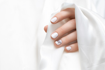 Female hand with white dandelion nail design.